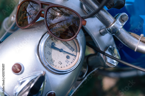 Fotobehang Fiets motorcycle parts headlight with sunglasses vintage retro motorbike. old timer age concept, 1960s style, outdoor dirt road