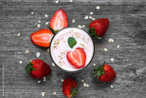 Fototapeta strawberry yogurt in a glass with fresh berries, oats and mint on rustic wooden background obraz