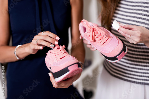 Fotografie, Obraz  Three young girlfriends examining holding new pair of sports footwear standing i