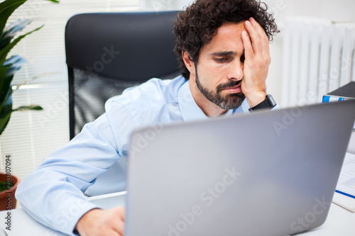 Tired businessman working in his office Poster