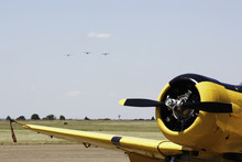 Yellow Aerobatic Harvard Aircraft With A Formation On Approach