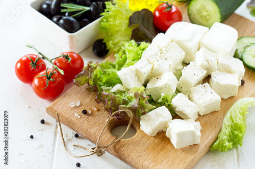 Feta cheese and black olives, cooking qreek salad with fresh vegetables on a white wooden table.