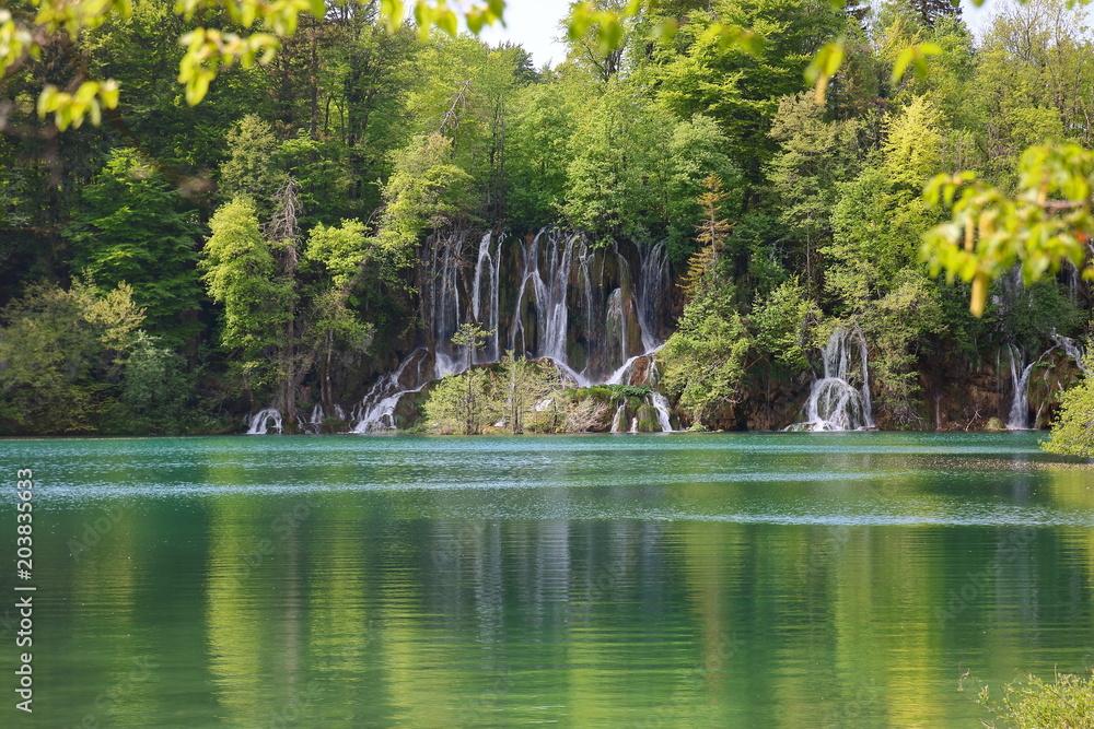 Fototapeta Piękny pejzaż szmaragdowego jeziora w Plitwickim Parku Narodowym w Chorwacji, wodospady, porośnięte bujną zielenią wzgórze