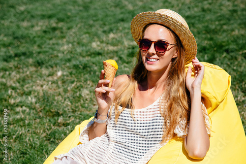Staande foto Kasteel Joyful smiling girl in sunglasses and hat, holds an ice-cream, relaxing on air sofa Lamzac, wearing stylish clothes, outdoors. Leisure concept.