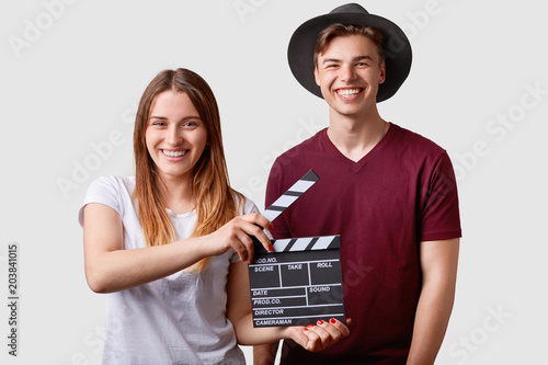 Photo  Two successful young female and male famous producers or directors hold film clapper, participate in shooting film, have joyful expressions, pose against white background