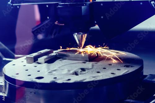 Fotografia  3D metal printer produces a steel part.