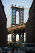 Brooklyn bridge seen from a narrow alley enclosed by two brick buildings during the sunset. New York City, USA.