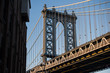 Close-up view of the Brooklyn bridge seen from a narrow alley during the sunset. New York City, USA.