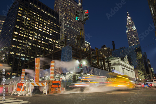 Foto op Plexiglas New York TAXI Long exposure photo of cars crossing an intersection in New York City while steam coming out from the manhole. Empire State building in the background, Manhattan, USA.