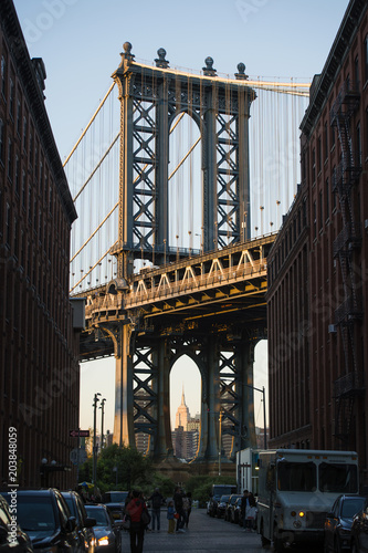 Foto op Canvas Brooklyn Bridge Brooklyn bridge seen from a narrow alley enclosed by two brick buildings during the sunset. New York City, USA.