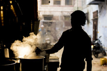 Silhouette Of An Indian Man Preparing The Famous Masala Chai. The Masala Chai Is A Flavoured Tea Beverage Made By Brewing Black Tea With A Mixture Of Aromatic Indian Spices And Herbs