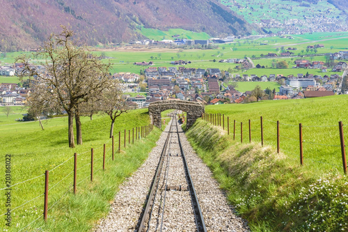 Trees and railway on the foot of Mt. Stanserhorn in Switzerland in the beginning of May. Mt. Stanserhorn is a mountain located in the Swiss canton of Nidwalden, near the town of Stans.