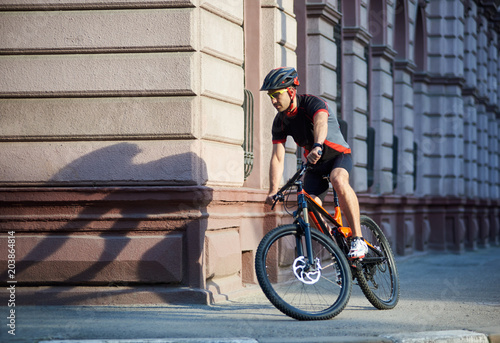 Bicyclist in professional cycling clothing and protective helmet riding  bicycle along old historical city streets 1dac3b6ec
