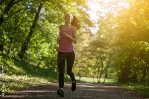 Young woman is jogging in park.