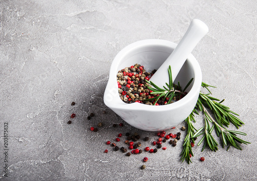 Foto op Canvas Kruiderij Pepper in white mortar and rosemary