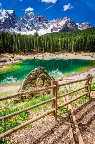 Fototapeta Big rock and green mountain Carezza lake in Dolomites, Italy obraz