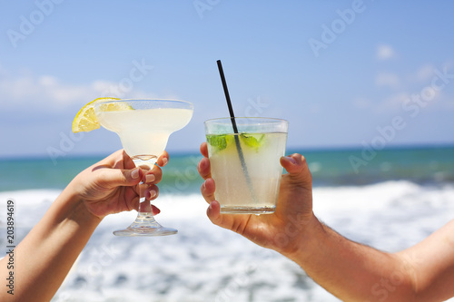 Tuinposter Cocktail Two cocktail glasses in man and woman hands