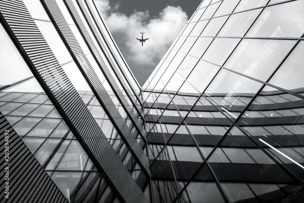 Fototapeta Flying airplane over modern architecture building, low angle black and white high contrast picture