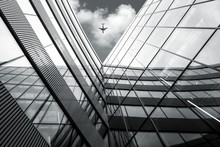 Flying Airplane Over Modern Architecture Building, Low Angle Black And White High Contrast Picture