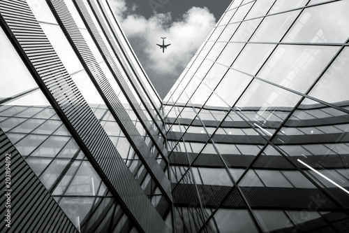 Keuken foto achterwand Stad gebouw Flying airplane over modern architecture building, low angle black and white high contrast picture