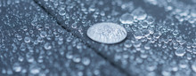 Closeup Detailed View Of Raindrops On A Fabric, A Background.