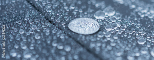 Fotobehang Stof Closeup detailed view of raindrops on a fabric, a background.