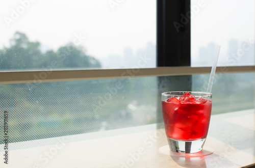 A Drink by the View of City Buildings and Trees