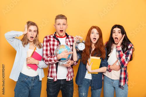 Papiers peints Fluvial Group of shocked school friends showing alarm clock