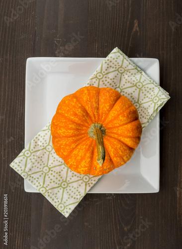 Bright Orange Pumpkin sits on Square Plate and Napkin