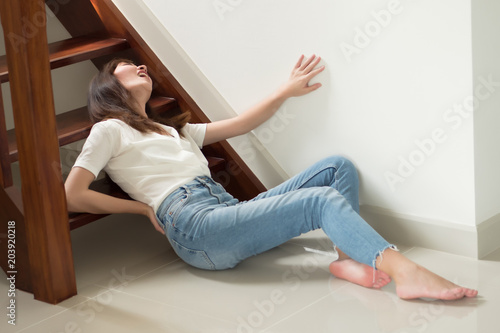 Fototapeta injured woman with hip pain or back injury; portrait of asian woman falling from stair, having pain at her back or hip, concept of pain or injury from accident; 30s adult asian woman model obraz