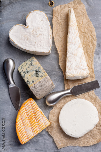 Poster Assortiment French cheeses plate in assortment, blue cheese, brie, munster, soft goat cheese, Neufchatel heart shaped cheese