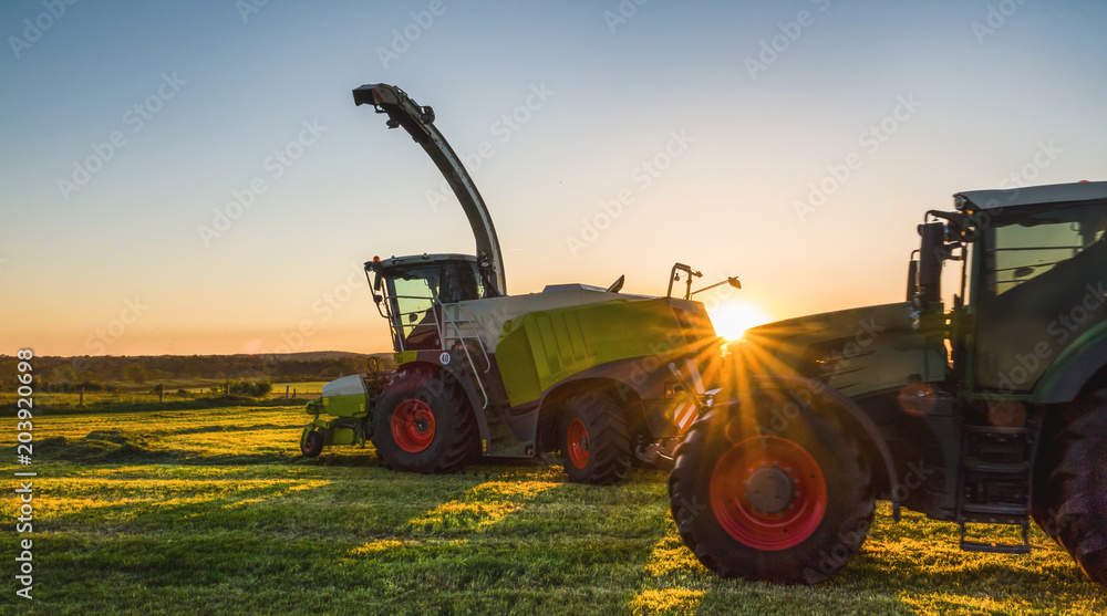 Tractor working agicultural machinery in sunny day
