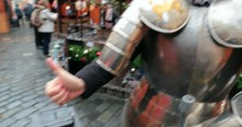 Woman Wearing Medieval European Armor. Girl Having Fun By Wearing Steel Armor In Touristic Attraction While Giving Thumbs Up And Smiling Posing To Camera