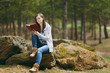 Young concentrated beautiful woman in casual clothes sitting on stone studying reading book in city park or forest on green blurred background. Student learning, education. Lifestyle, leisure concept.