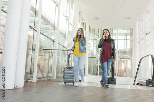 Garden Poster Martial arts beautiful young women talking on her mobile phone and smiling. Travel concept at the airport, She is going up stairs with a trolley. Friends and lifestyle