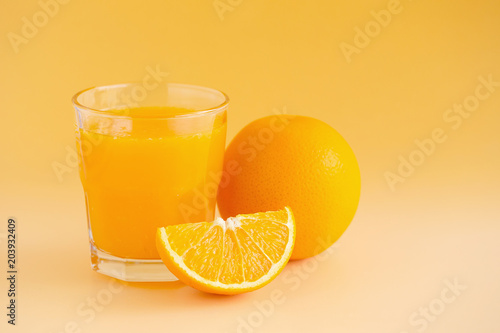 Foto op Canvas Sap Glass of orange juice freshly squeezed on an orange background