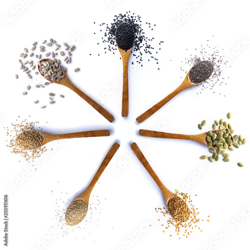 Composition of spoons with seeds on white background