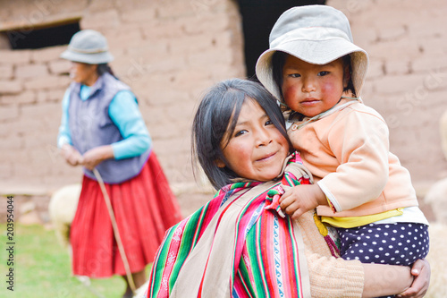 Fotografía  Native american girl with typical aymara cloth holding her little sister outside