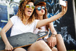 canvas print picture Two female skaters friends sitting on ramp and hangout at the skate park .Taking selfie.