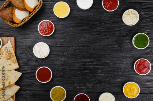 Foto op Canvas Kruiderij Assorted sauces on a black wooden background with copy space
