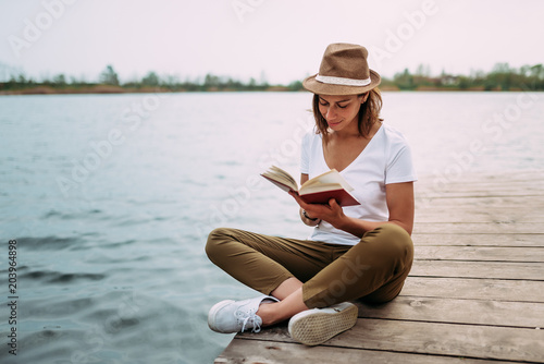 Fototapeta Portrait of a girl reading a book while sitting on a small wooden wharf