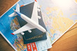 Leinwandbild Motiv Plane model with world map, passports and tickets as airplane traveling and tickets booking concept