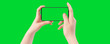 canvas print picture - Female hands holding smartphone with empty screen, isolated on green background. The chromakey. Green screen.