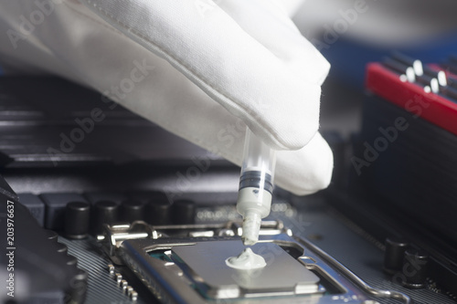 Fotografie, Obraz Hand wearing White Gloves with syringe applying thermal paste on the CPU process