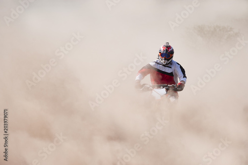 Poster Motorise Motocross rider racing in a large cloud of dust and debris