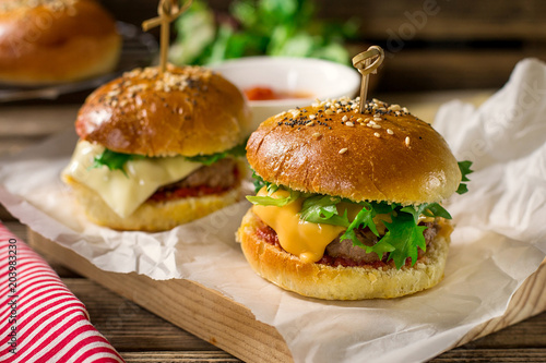 Mini cheeseburgers sliders with ground beef, cheddar, lettuce and tomato sauce