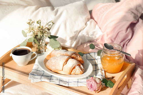Tray with delicious croissants, cup of coffee and honey on bed