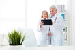 Mature female receptionist and senior male doctor working in hospital