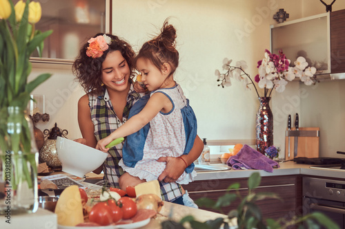 Photo  Beautiful Hispanic mother teaches her cute little daughter prepare pizza in the kitchen