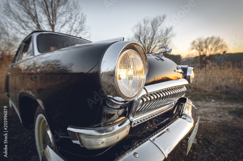classic vintage retro black car closeup view from bumper and lamp on sunset Canvas Print